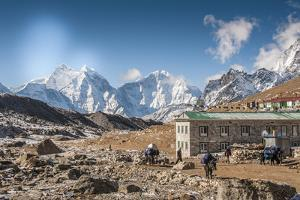 Trekkers and yaks in Lobuche on a trail to Mt. Everest. by Lee Klopfer