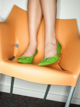 Legs and Feet of Woman in Lime Green Pointed Shoes Standing in a Modern Orange Plastic Chair