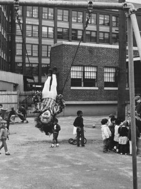 Child on Swings in Playground at the KLH Day Care Center by Leonard Mccombe