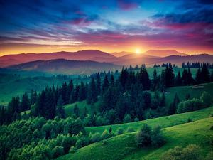Green Hills Glowing by Warm Sunlight at Twilight. Dramatic Scene. Colorful Sky, Red Clouds. Carpath by Leonid Tit