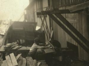 Dangerous Work - 12-Year Old Laborer at Miller and Vidor Lumber Company, Beaumont, Texas, c.1913 by Lewis Wickes Hine