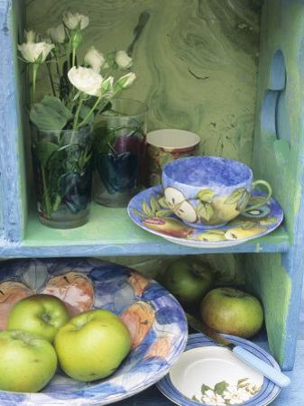 Coffee Cup, Flowers and Bowl of Apples on Shelves by Linda Burgess