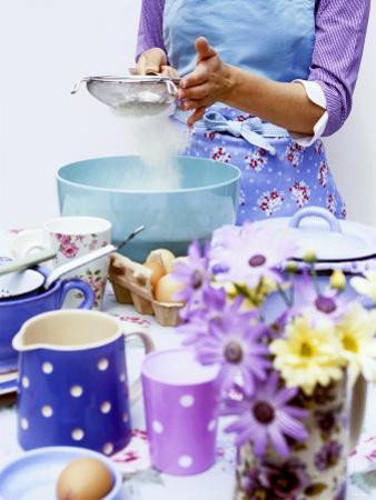 Woman Sieving Flour into a Bowl, Crockery & Eggs in Front by Linda Burgess