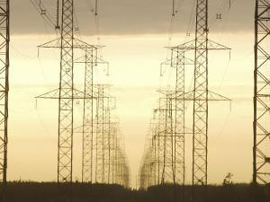 Line of High Tension Industrial Electrical Towers at Dusk