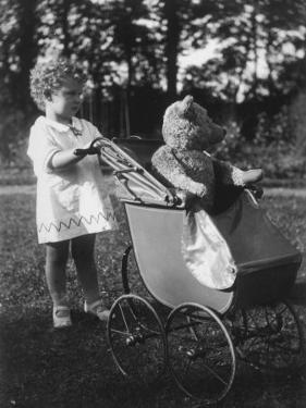 Little Girl Pushes Her Teddy Bear Around in a Pram
