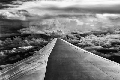 Wing of Airplane Flying in Mid-Air under and Between Clouds