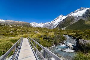 A hiking trail crosses wooden bridge over a creak high up in the mountains, New Zealand by Logan Brown