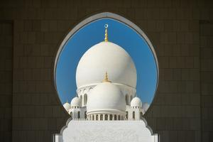A mosque is framed by an arched passageway in Abu Dhabi, United Arab Emirates, Middle East by Logan Brown