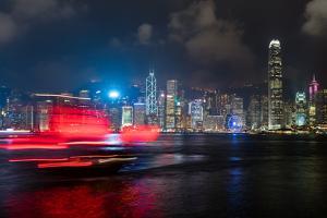 A red junk sailboat glides in front of the Hong Kong skyline at night, Hong Kong, China, Asia by Logan Brown