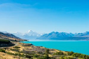 A road winds along the edge of a turquoise blue lake with mountains in the distance, New Zealand by Logan Brown