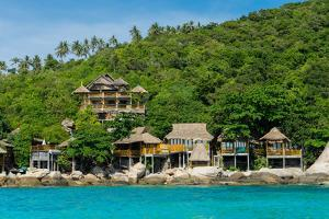 A traditional Thai resort overlooks turquoise water on the tropical island of Koh Tao, Thailand by Logan Brown