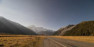 Late afternoon sun over a long straight road into the mountains, South Island, New Zealand, Pacific by Logan Brown