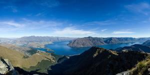 Steep sharp mountains, a deep blue lake, and mountain town in Queenstown, Otago, New Zealand by Logan Brown