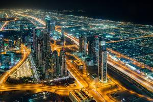 The street lights and skyscrapers of Dubai from high above the city, Dubai, United Arab Emirates by Logan Brown