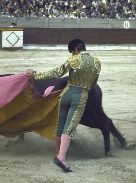 "Bullfighter Manuel Benitez, Known as ""El Cordobes,"" Sweeping His Cape Aside the Charging Bull by Loomis Dean"