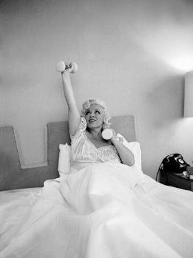 Entertainer Mae West Lifitng Barbells in Bed by Loomis Dean