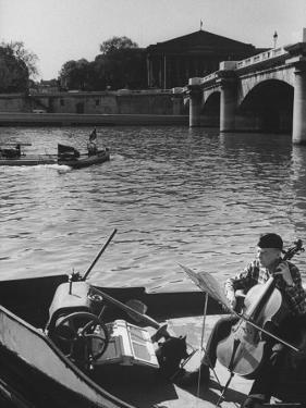 Man Playing Cello on Boat by Loomis Dean