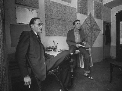 Painter Brion Gysin, Shown W His Paintings in Hotel Room in with Writer William S. Burroughs