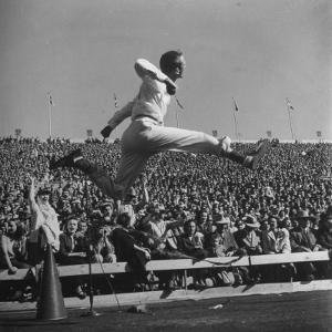 Smu Cheerleader Leaping High into Air at University of Texas Football Game by Loomis Dean