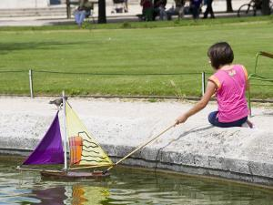 Girl with Toy Boat in Pond of Jardin Des Tuileres by Lou Jones