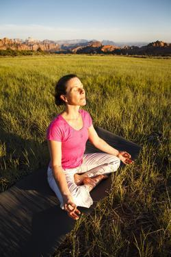 A Woman Practices Sunset Yoga in Lee Valley, Zion National Park, Utah by Louis Arevalo