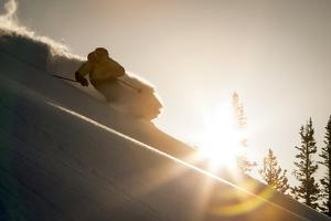 A Young Skier Chases the Sun Down the Ski Slope in the Wasatch Backcountry, Utah by Louis Arevalo