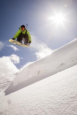 A Young Snowboarder Catching Air in the Wasatch Backcountry, Utah by Louis Arevalo