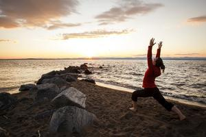 A Young Woman Welcomes the Sun by Practicing Yoga at Ausable Beach, Lake Champlain, New York by Louis Arevalo