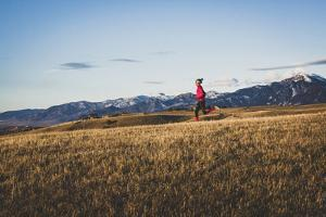 Inge Perkins Out For A Winter Sunset Run On Triple Tree Trail, Bozeman, Montana. Bridger Range Bkgd by Louis Arevalo