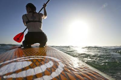 Woman on Stand Up Paddle-Board Heads into the Sunset at San Onofre Beach, San Clemente, California