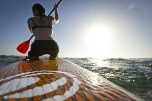 Woman on Stand Up Paddle-Board Heads into the Sunset at San Onofre Beach, San Clemente, California by Louis Arevalo