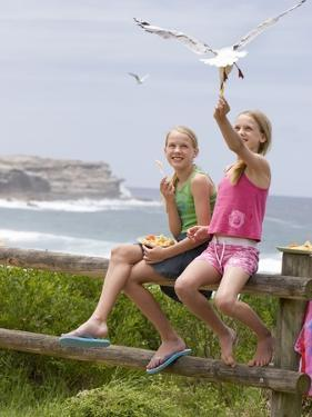 Two Girls Feeding Chips to a Seagull at the Beach by Louise Hammond
