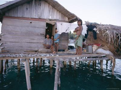 Bajau Family in Stilt House Over the Sea, with Fish Drying on Platform Outside, Sabah, Malaysia by Lousie Murray