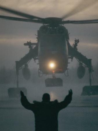 A Man Guides a Landing Helicopter by Lowell Georgia