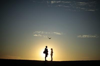 A Couple Stands on a Sand Bank as the Sun Sets in Venice, Los Angeles