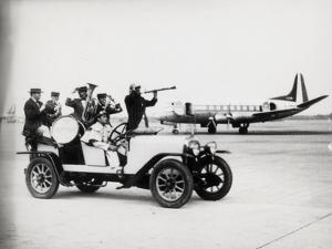 A Vintage Car with a Welcoming Band at the Airport by Luigi Leoni