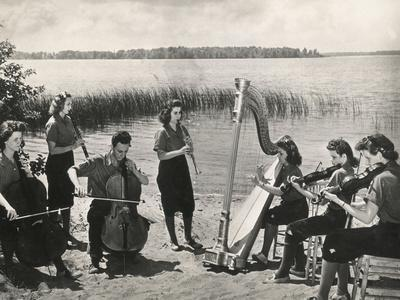 Young Musicians at a Concert on the Banks of a Lake