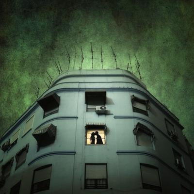 Silhouette of a Man and Woman Kissing in a Window of a Large Building with TV Ariels on the Roof
