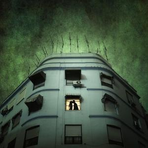 Silhouette of a Man and Woman Kissing in a Window of a Large Building with TV Ariels on the Roof by Luis Beltran