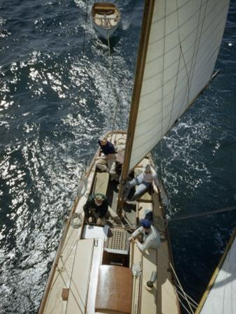 Sailors Sit in Sun on Deck of Sailboat Underway in a Good Breeze