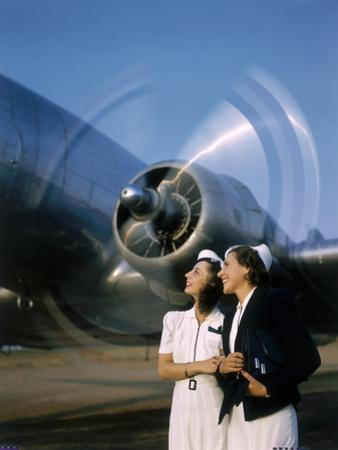 Two Young Women Stand Near a Turning Aircraft Propeller