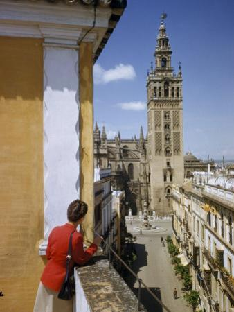 Woman Stands on Terrace Overlooking Street Leading to the Giralda