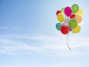 Colorful Bunch of Balloons Floating in the Sky by Luxx Images