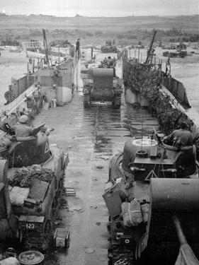 M4 Sherman Tanks with Exhaust Stacks Driving Off a Landing Craft Towards a Beach