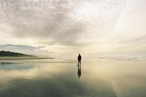 A Person Walks on the Beach before a Midday Storm by Macduff Everton