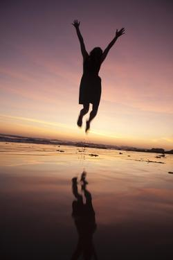 A Woman Jumping on the Beach at Sunset by Macduff Everton