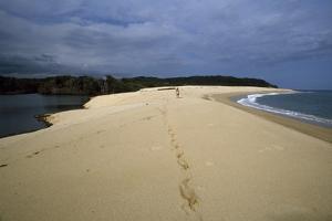 A Woman Walks on the Beach, Leaving Footprints Near a Lagoon at Playa Cacaluta by Macduff Everton