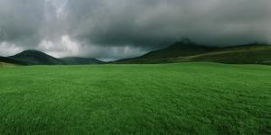 Thick Low Hanging Clouds Above Dark Hills and a Bright Green Field by Macduff Everton