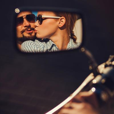 Carefree Young Couple in Sunglasses Kissing Reflected in the Mirror of a Motorcycle by Maksim Ladouski