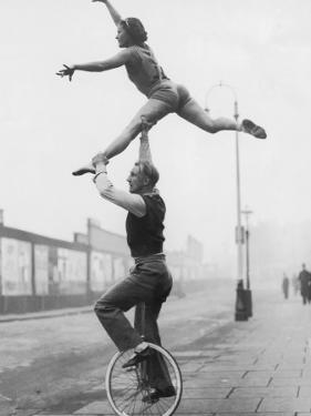Male Acrobat on Unicycle Supporting Woman in Air